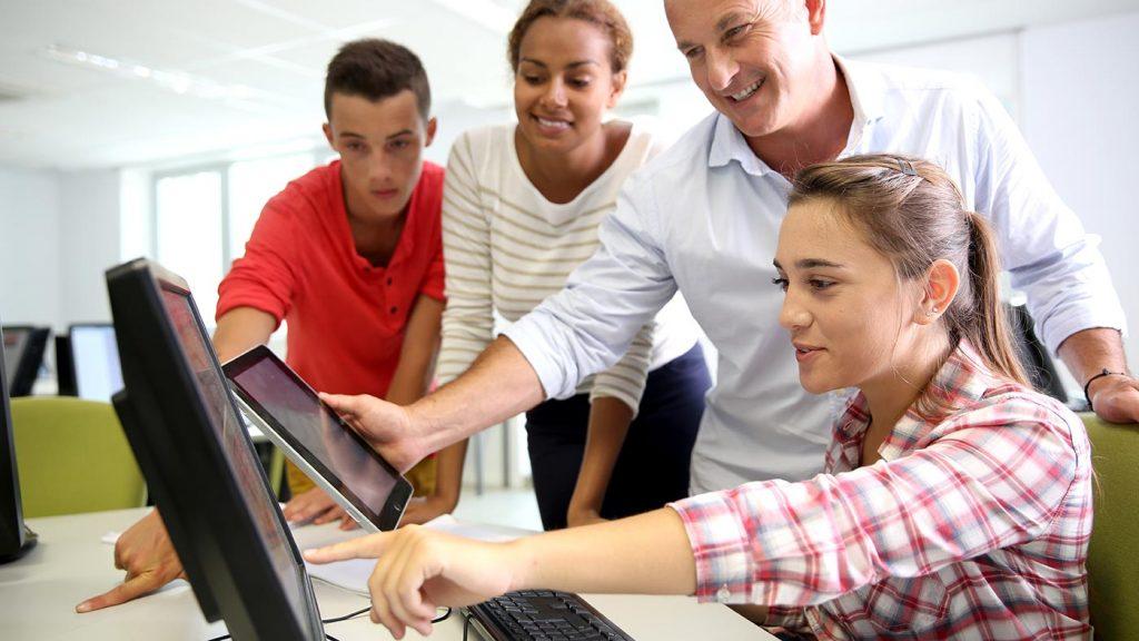 Schüler und Lehrer eines Berufsbildungswerks schauen gemeinsam lächelnd auf den Monitor