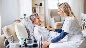 Mobile Pflegekraft untersucht ältere und kranke Frau im Bett liegend