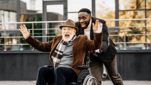 Persönliche Assistent eines älteren Mannes schiebt schnell und gut gelaunt seinen Klienten im Rollstuhl