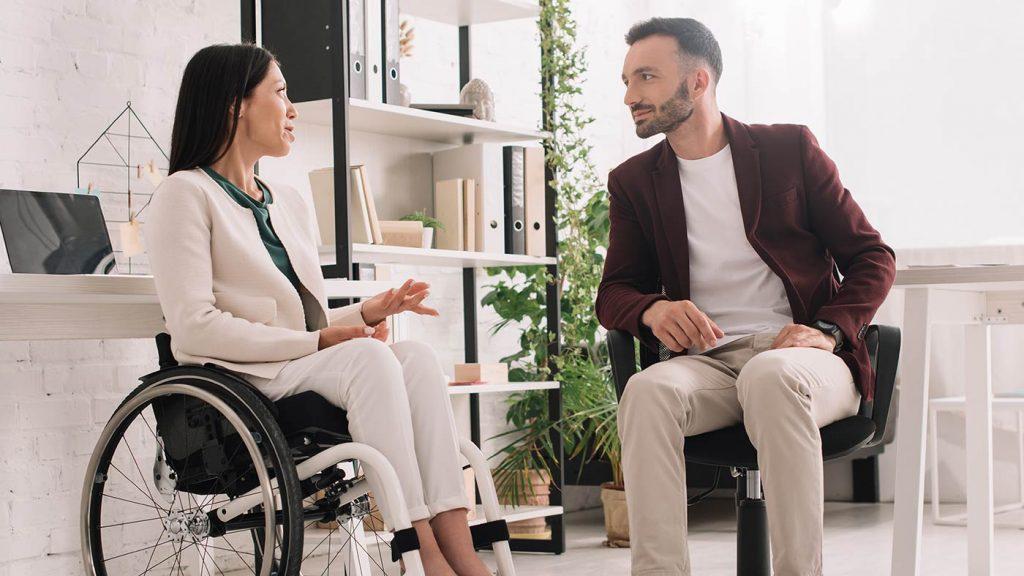 Arbeitergeberin im Rollstuhl instruiert ihren persönlichen Assistenten