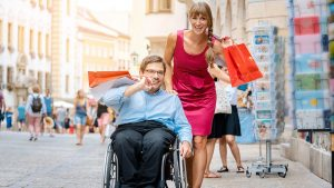 Rollstuhlfahrer zusammen mit seiner Assistentin gut gelaunt und lachend beim Einkaufen