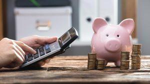 Taschenrechner berechnet das persönliche Budget während auf dem Tisch davor ein rosa Glückschwein und mehrere Münzstapel stehen