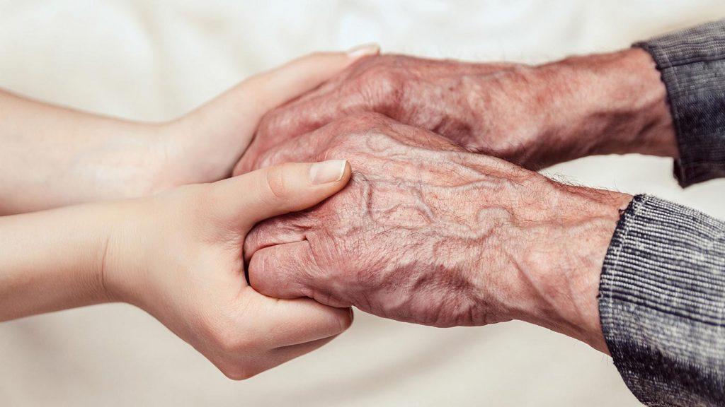 Hände eines alten Mannes und einer jungen Frau halten einander vertrauensvoll