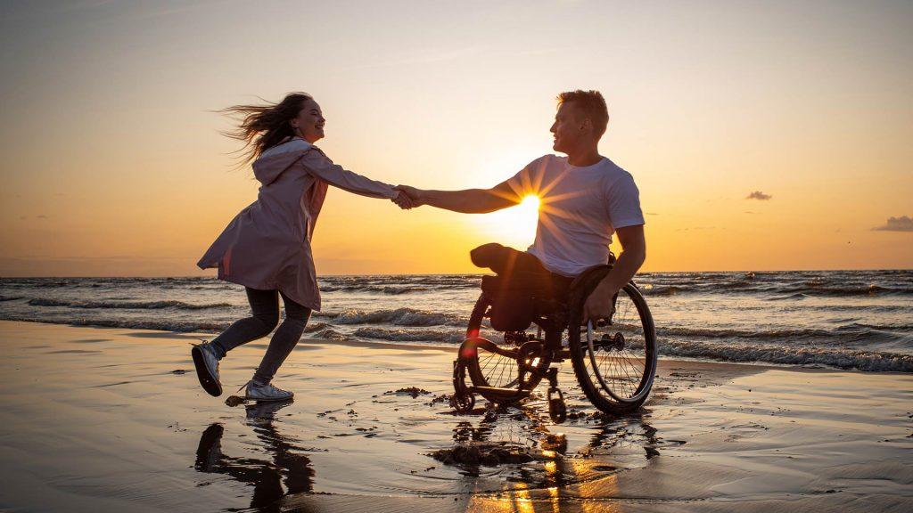 Mann im Rollstuhl und Frau tanzen gemeinsam am Strand und genießen das Leben mit Behinderung