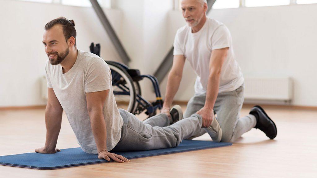 Querschnittgelähmter Mann bei der Physiotherapie mit seinem Therapeuten