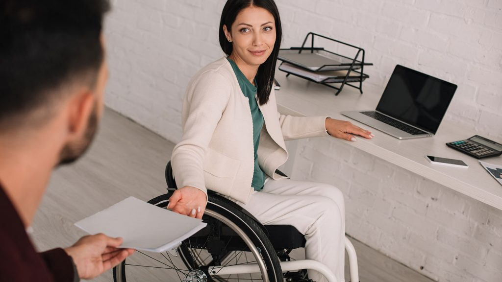 Rollstuhlfahrende Arbeitgeberin übergibt ihrem Assistenten ein Arbeitsdokument