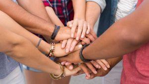 Freunde stapeln ihre Hände übereinander als Zeichen von Gemeinschaft und Vielfältigkeit