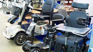 Elektrorollstühle und E-Scooter stehen ausgestellt in Reihe