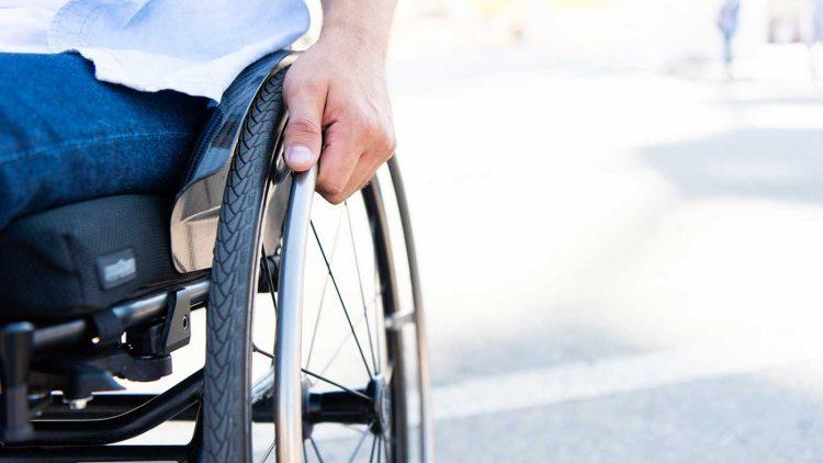 Mann im Rollstuhl umfasst die Greifringe seines Rollstuhl