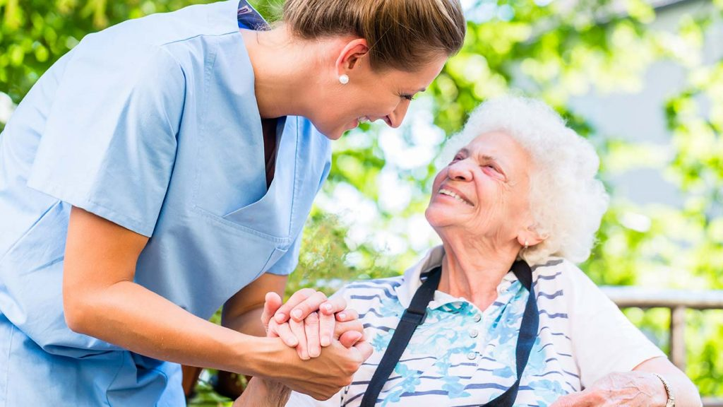 Altenpflegerin umgreift vertrauensvoll die Hand einer Seniorin im Rollstuhl