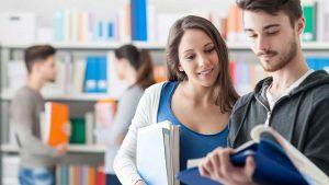 Zwei Studierende schauen in der Bibliothek gemeinsam glücklich in ein Buch